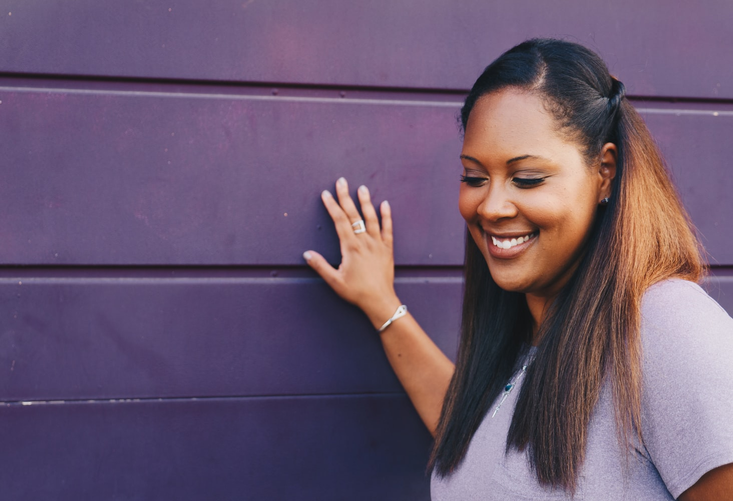 Claudia smiling against a purple wall